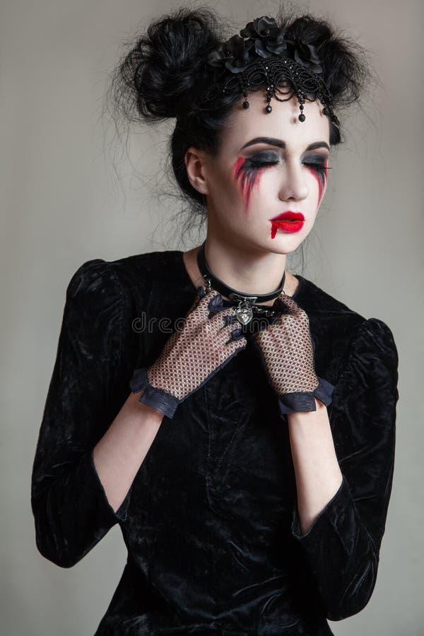 Mulher gótico bonita nova com os bordos brancos da pele e do vermelho Halloween imagens de stock
