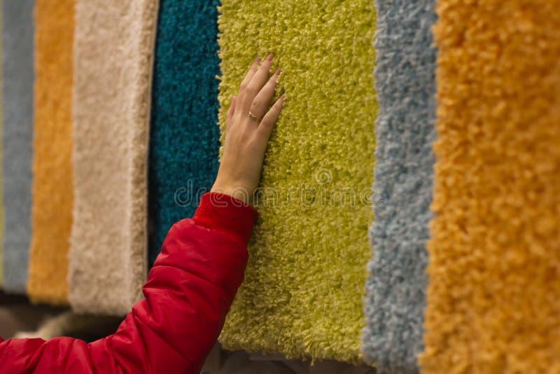 A mulher gasta a compra e seleciona os tapetes do luxuoso à mão na loja fotografia de stock royalty free