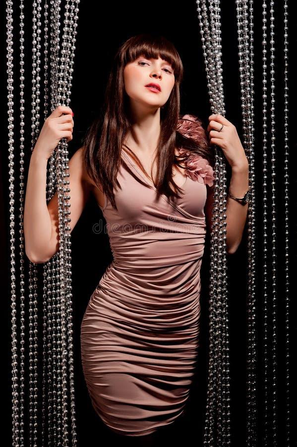 Mulher glamoroso no vestido que levanta perto das cortinas imagens de stock royalty free