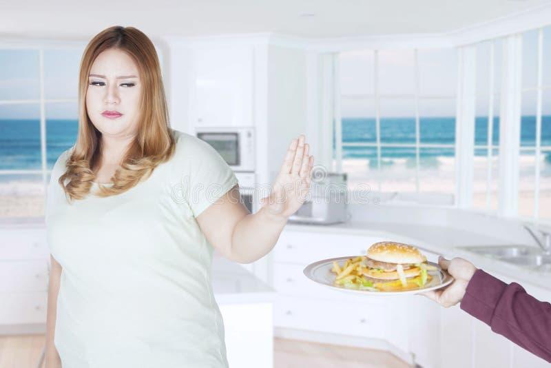 Mulher gorda com comida lixo na cozinha imagem de stock