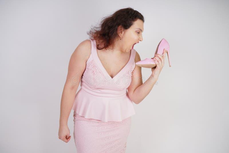 Mulher gorda emocional na fala e nas bisbolhetices cor-de-rosa do vestido na sapata como no telefone em um fundo branco do estúd fotos de stock
