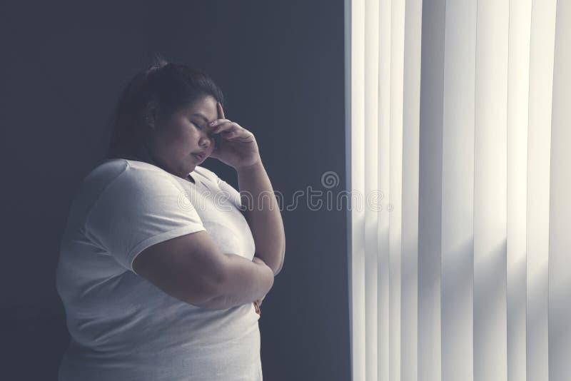 Mulher gorda forçada que está pela janela fotografia de stock