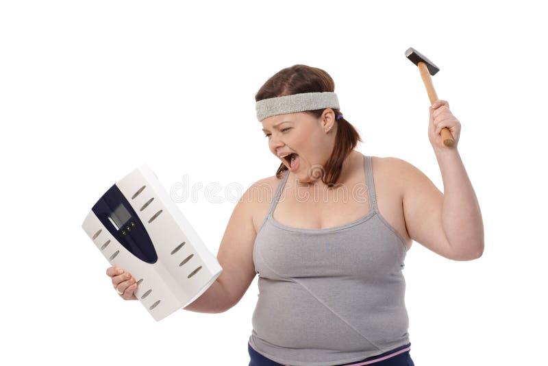 Mulher gorda irritada com martelo e escala imagem de stock royalty free