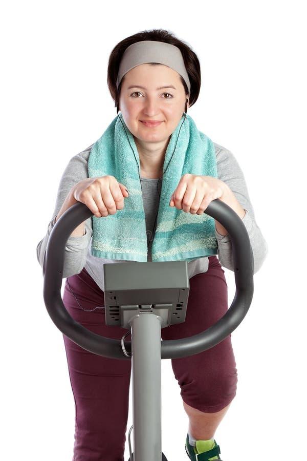 A mulher gorda perde o peso que reune a gordura em uma bicicleta estacionária. fotografia de stock
