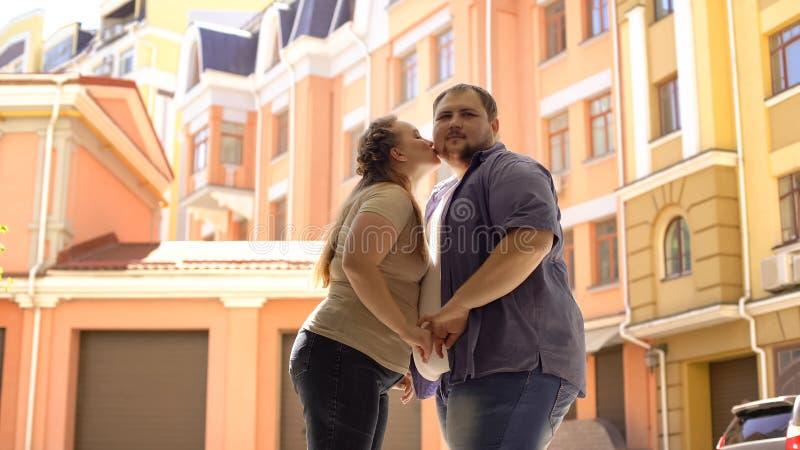 Mulher gorda que beija o noivo no mordente durante a data romântica, tomando a primeira etapa imagem de stock