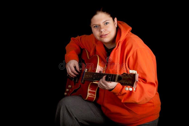 Mulher gorda que joga na guitarra elétrica alaranjada imagem de stock royalty free