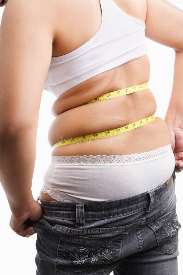Mulher gorda que tenta desgastar calças de brim apertadas da parte traseira fotos de stock