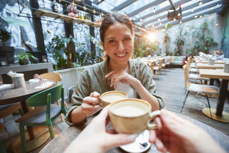 Mulher gostando de café com amigo imagem de stock