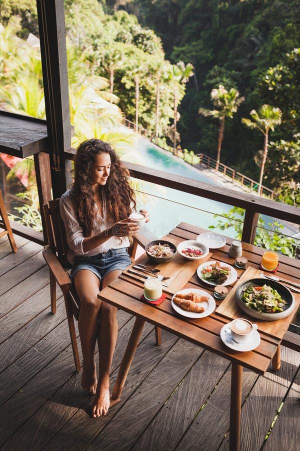 Mulher gostando do café da manhã, terraço com vista para a selva imagem de stock