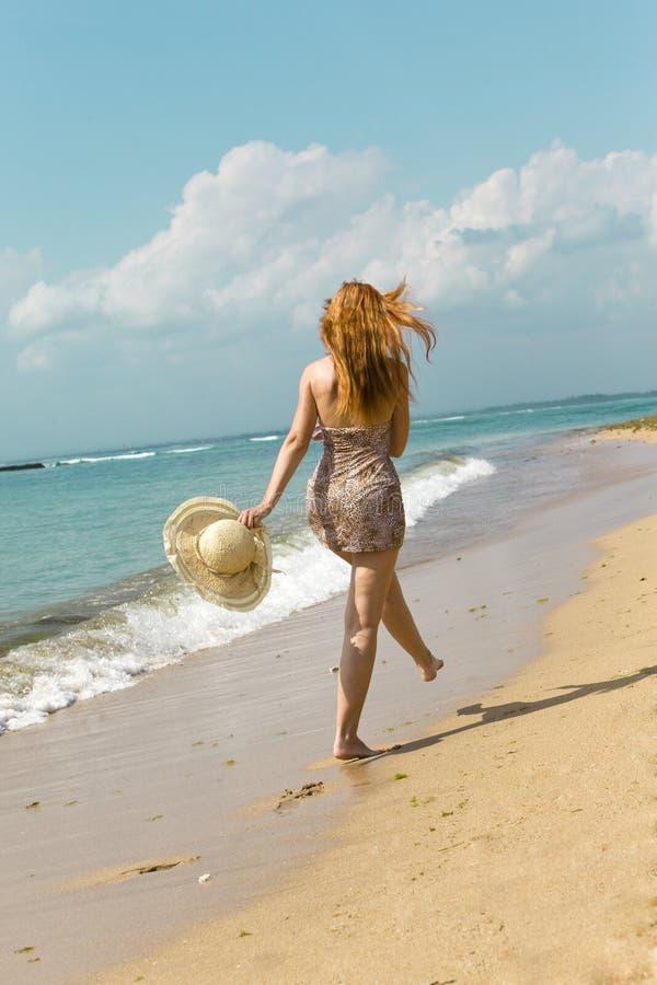 A mulher graciosa nova vai na costa do oceano imagens de stock royalty free