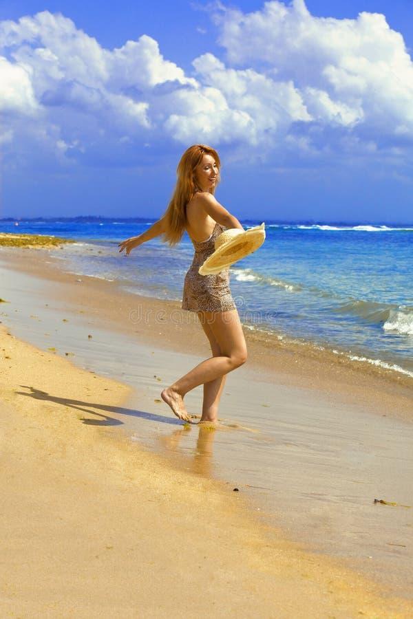 A mulher graciosa nova vai na costa do oceano foto de stock