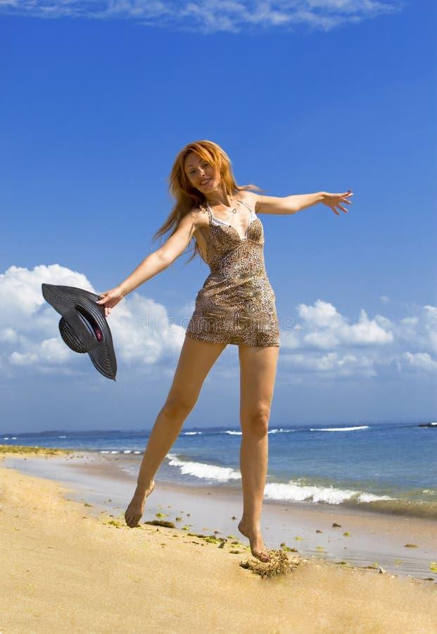 A mulher graciosa nova vai na costa do oceano fotografia de stock royalty free