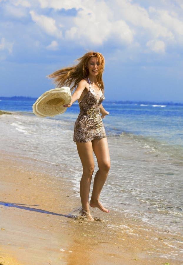 A mulher graciosa nova vai na costa do oceano imagem de stock royalty free