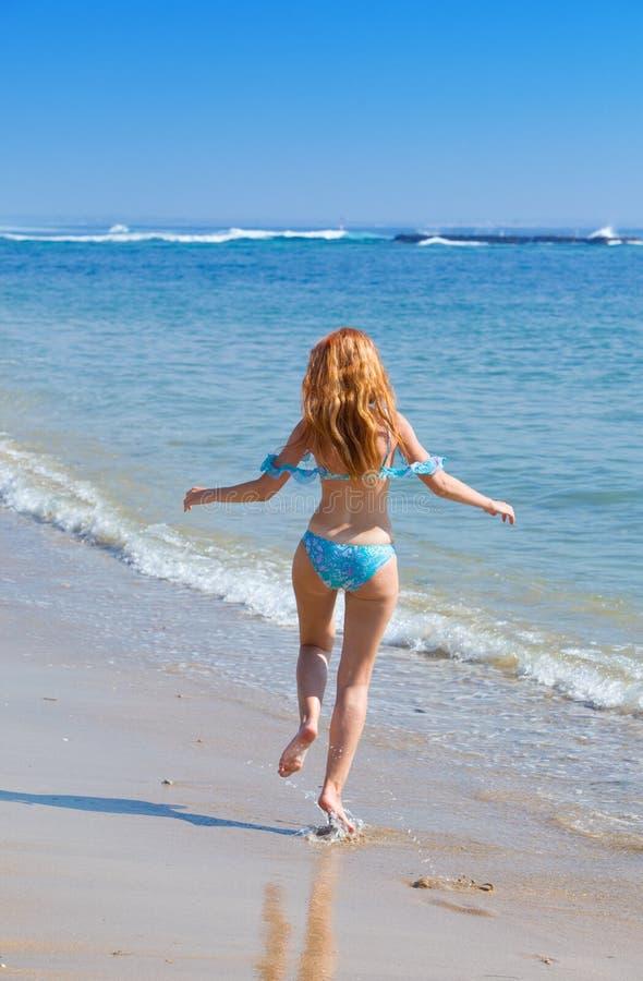 A mulher graciosa nova vai na costa do oceano imagens de stock