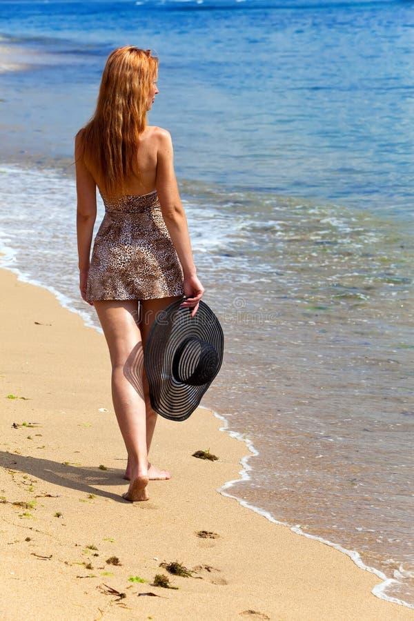 A mulher graciosa nova vai na costa do oceano fotos de stock royalty free