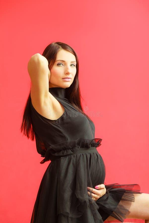 Mulher gravida à moda no preto fotos de stock royalty free
