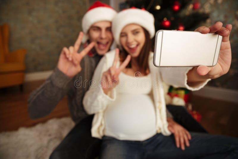 Mulher gravida animador de sorriso com seu marido que comemora o Natal ao sentar-se junto em um assoalho e ao tomar um selfie em  foto de stock