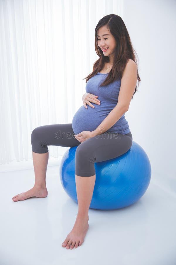 Mulher gravida asiática bonita que faz o exercício com uma bola suíça, fotografia de stock royalty free