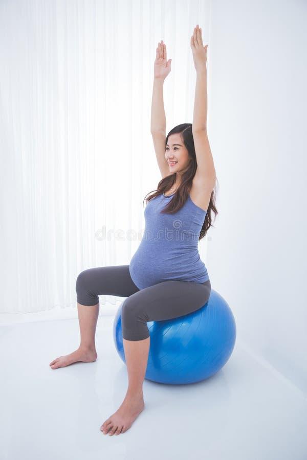 Mulher gravida asiática bonita que faz o exercício com uma bola suíça, imagem de stock