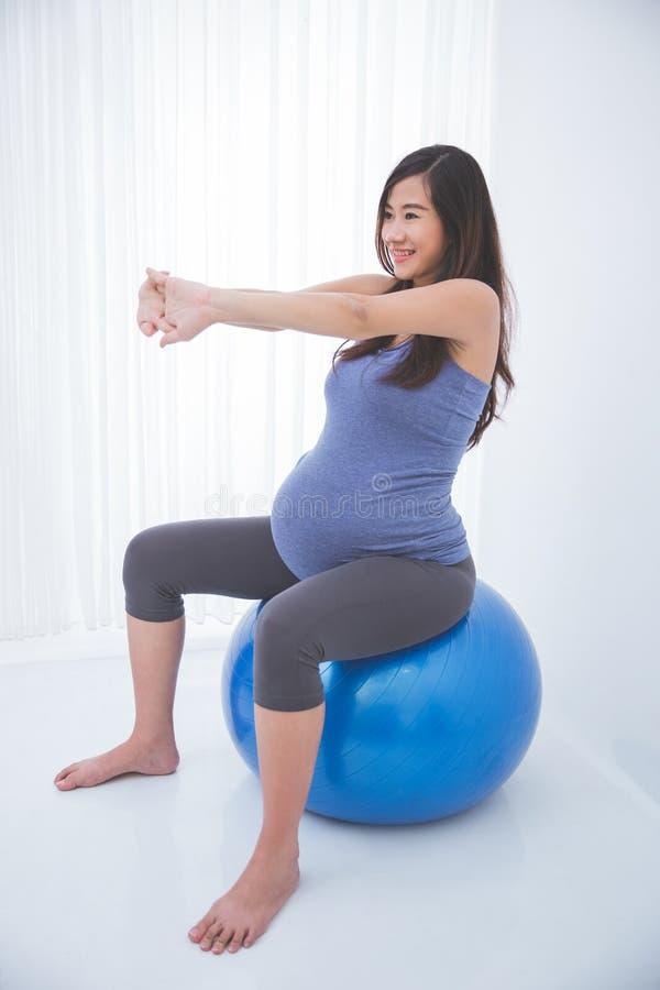 Mulher gravida asiática bonita que faz o exercício com uma bola suíça, fotografia de stock