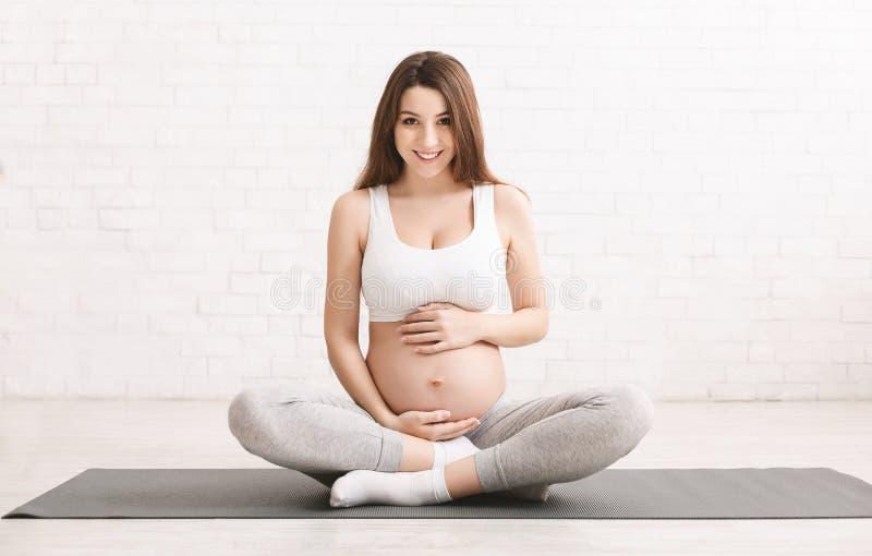 Mulher gravida ativa que senta-se no assoalho após ter feito esportes fotos de stock
