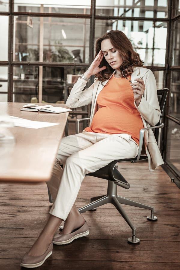 Mulher gravida bonita cansado que decola seus vidros e que fricciona o templo fotos de stock