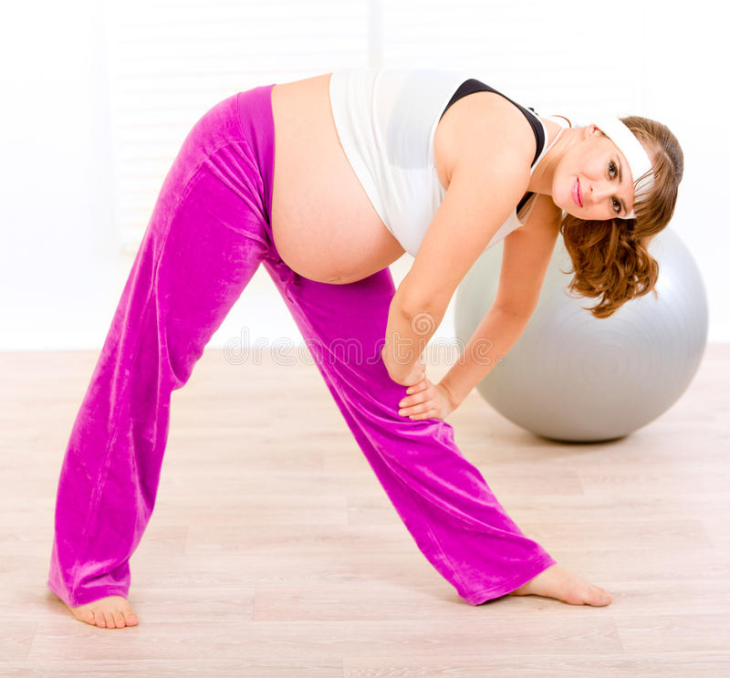 Mulher gravida bonita de sorriso que faz o exercício imagem de stock