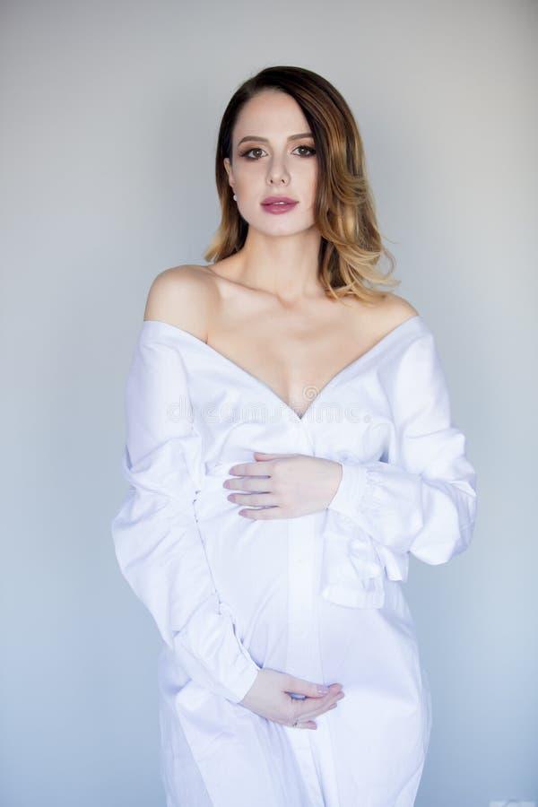 Mulher gravida bonita do ruivo no vestido branco fotos de stock