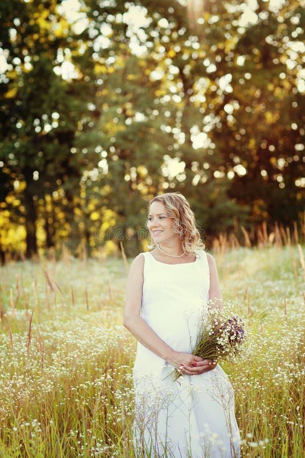 Mulher gravida bonita e feliz em um vestido branco na natureza no verão, em torno das árvores e das flores fotografia de stock