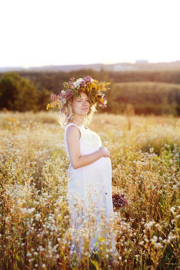 Mulher gravida bonita e feliz em um vestido branco na natureza no verão, em torno das árvores e das flores fotos de stock