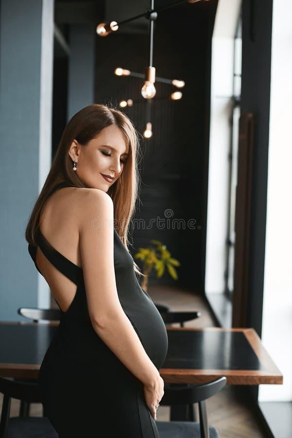 Mulher gravida bonita e nova em um vestido de nivelamento preto à moda que levanta no interior escuro minimalista do luxo foto de stock