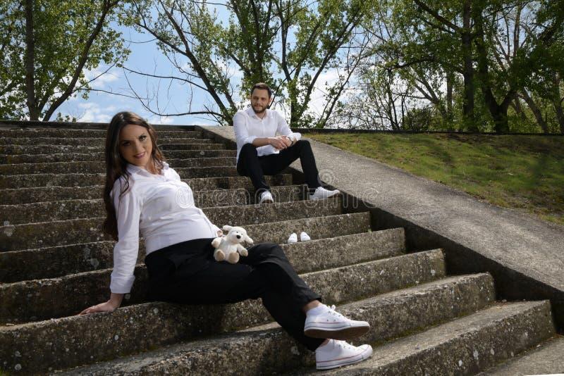 Mulher gravida bonita e seu marido que sentam no as escadas de pedra imagem de stock royalty free