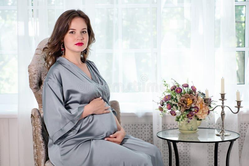 Mulher gravida bonita na expectativa que senta-se na poltrona pela janela fotos de stock