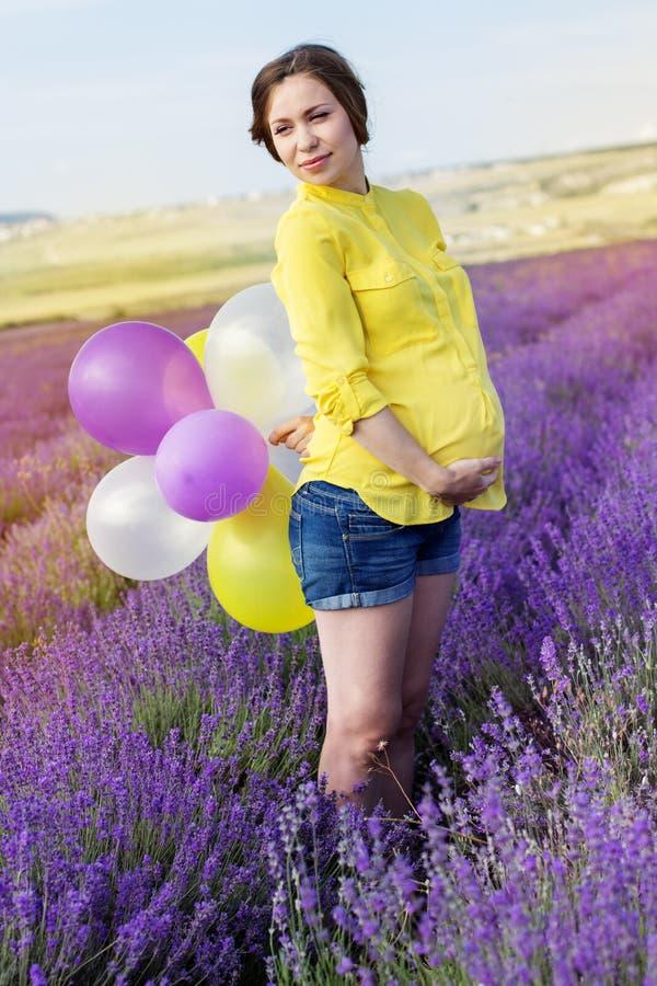 Mulher gravida bonita no campo da alfazema fotos de stock
