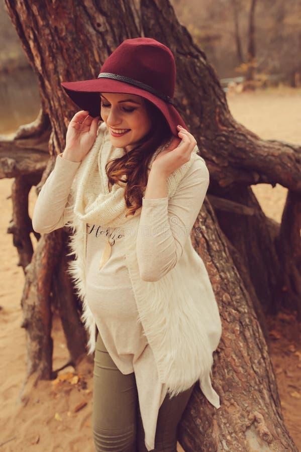Mulher gravida bonita no chapéu da forma na caminhada exterior morna acolhedor imagem de stock royalty free