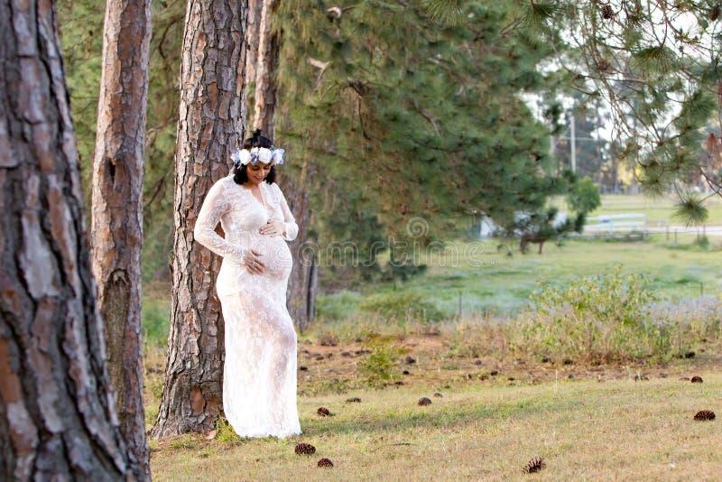 Mulher gravida bonita no vestido de maternidade do laço branco fora fotografia de stock