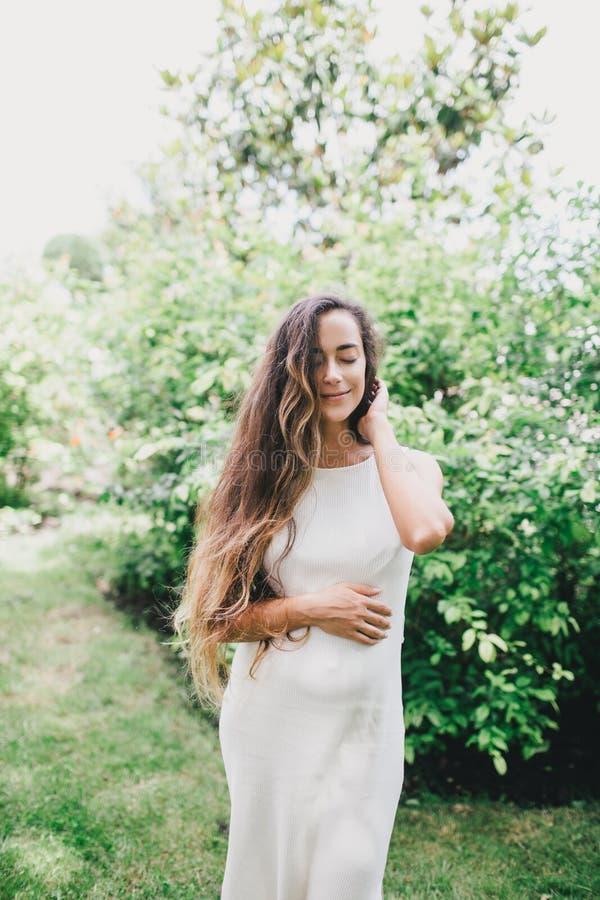 Mulher gravida bonita nova com o cabelo encaracolado saudável longo que levanta em um parque verde fotografia de stock royalty free