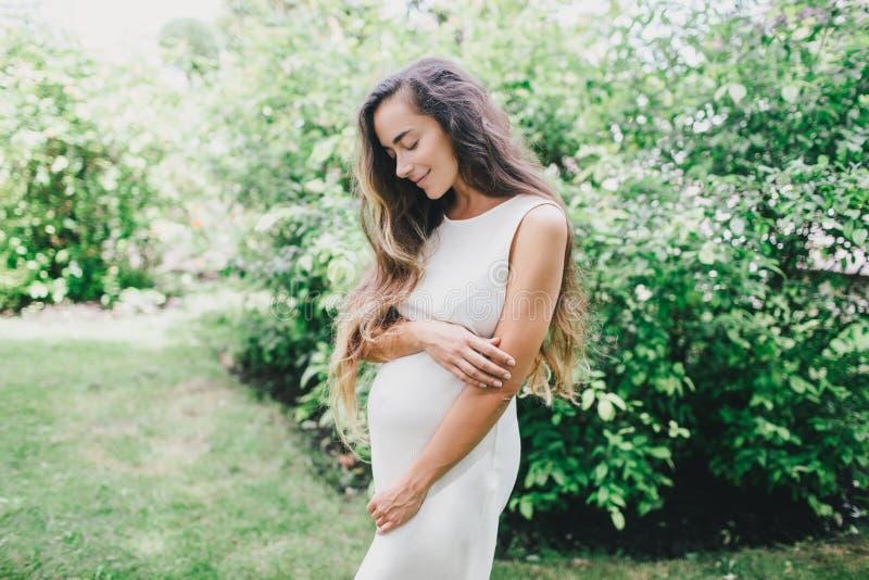 Mulher gravida bonita nova com o cabelo encaracolado saudável longo que levanta em um parque verde imagem de stock