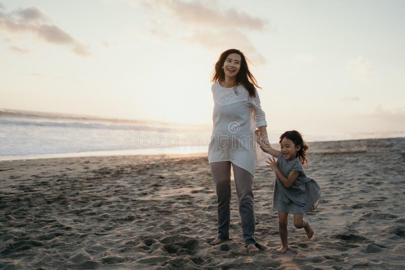 Mulher gravida bonita nova com sua filha bonito pequena que joga na praia imagem de stock royalty free