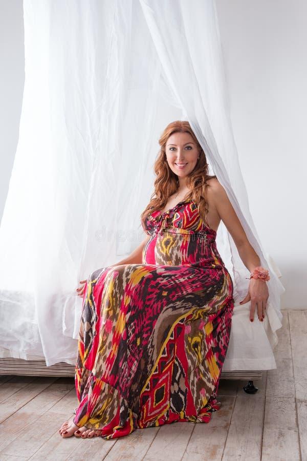 Mulher gravida bonita nova da forma no vestido colorido que senta-se em uma cama fotos de stock royalty free