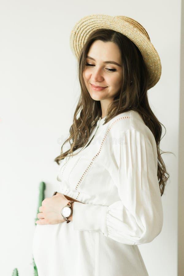 Mulher gravida bonita nova na posição do chapéu perto da parede branca foto de stock royalty free
