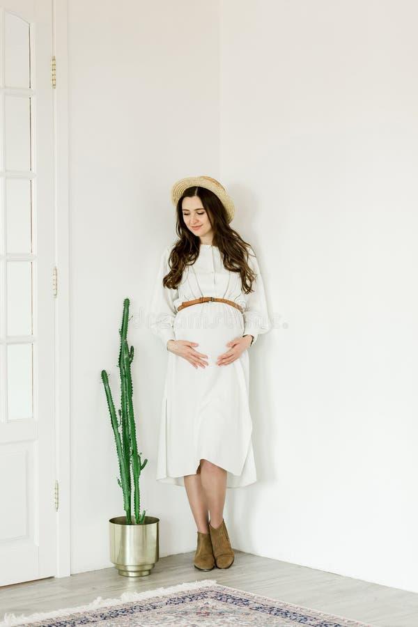 Mulher gravida bonita nova na posição do chapéu perto da parede branca imagem de stock