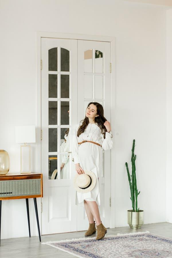Mulher gravida bonita nova na posição do chapéu perto da parede do cacto foto de stock royalty free