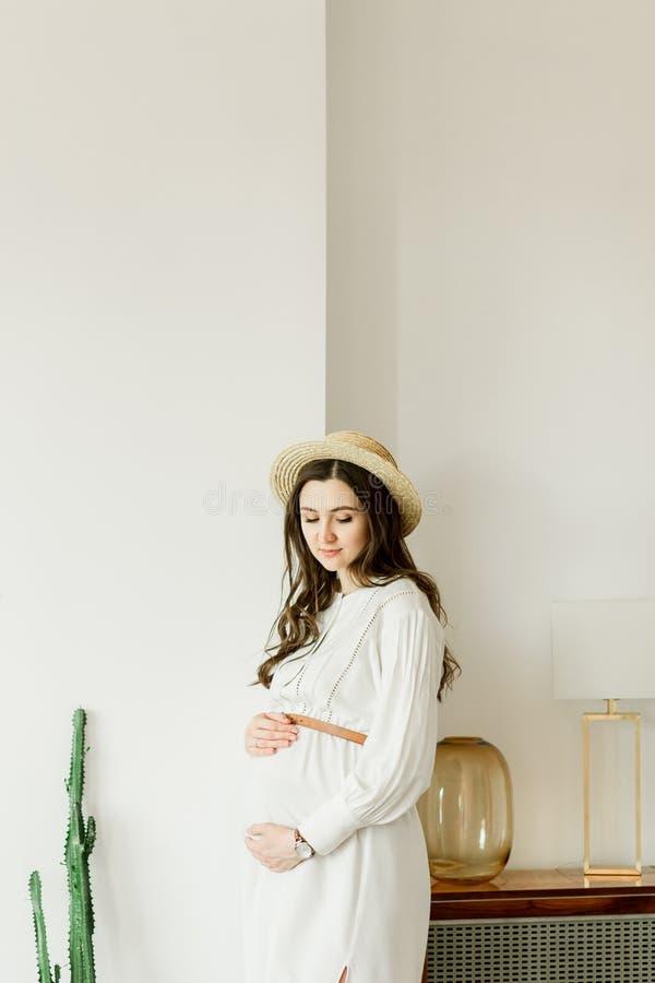Mulher gravida bonita nova na posi??o do chap?u perto da parede do cacto imagens de stock royalty free