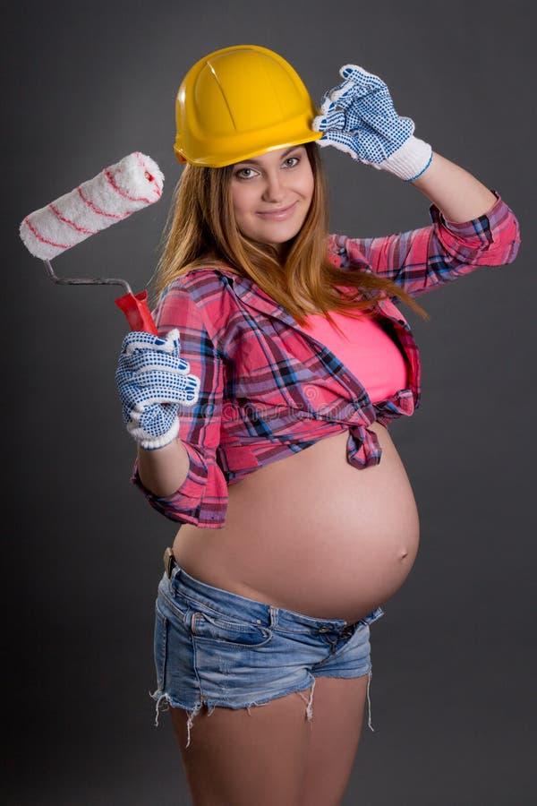 Mulher gravida bonita nova no capacete do construtor com pintura b fotografia de stock