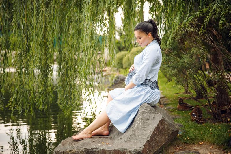 Mulher gravida bonita nova que relaxa nas rochas pelo lago no fundo no verão fotos de stock royalty free