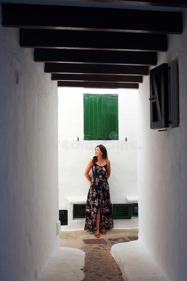 Mulher gravida bonita nova que relaxa-se no maravilhoso quando ruas muradas de uma vila mediterrânea na ilha de Menorca fotos de stock