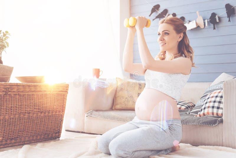 Mulher gravida bonita positiva que faz exercícios do esporte fotografia de stock