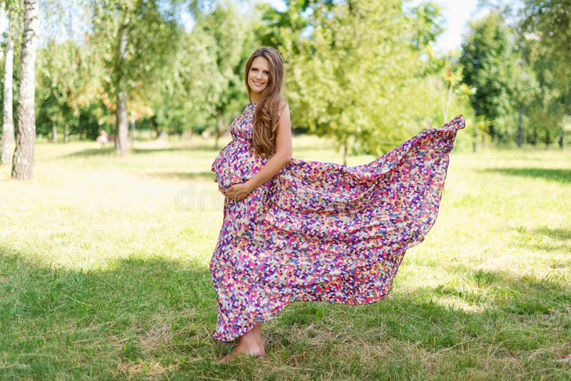 Mulher gravida bonita que anda no parque no vestido colorido longo com tela do voo fotos de stock