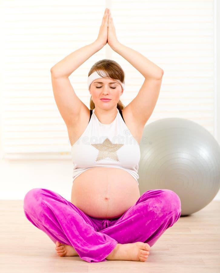 Mulher gravida bonita que faz a ioga no assoalho foto de stock royalty free